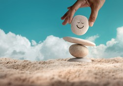 Enjoying Life Concept. Harmony and Positive Mind. Hand Setting Natural Pebble Stone with Smiling Face Cartoon to Balance on Beach Sand. Balancing Body, Mind, Soul and Spirit. Mental Health Practice