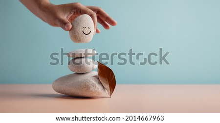 Enjoying Life Concept. Harmony and Positive Mind. Hand Setting Natural Pebble Stone with Smiling Face Cartoon to Balance. Balancing Body, Mind, Soul and Spirit. Mental Health Practice