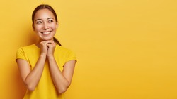 Enjoying life concept. Pleasant looking glad Asian woman looks aside, has toothy smile, keeps hands together under chin, dreams about something, wears casual clothing, isolated on yellow wall.