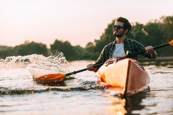 Enjoying life on river. Handsome young smiling man splashing water while kayaking on river