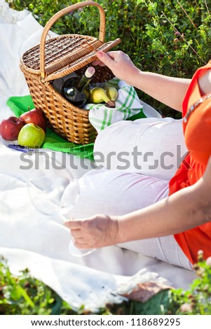 Enjoying lunch with red wine and fruits, picnic outdoors