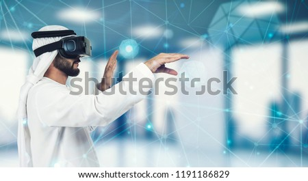 Enjoying new experience. Handsome Arab man in VR headset gesturing while standing against grey background