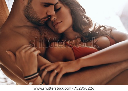 Photo of  Enjoying nice weekend together.  Beautiful young couple embracing while resting on the beach together
