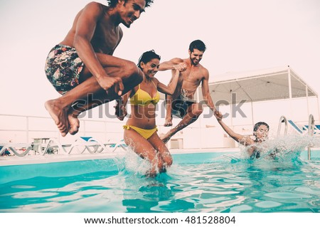 Enjoying pool party with friends. Group of beautiful young people looking happy while jumping into the swimming pool together #481528804