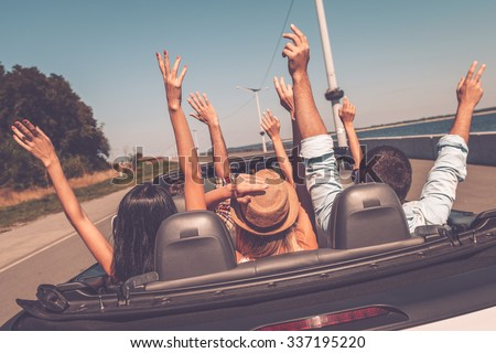 Enjoying road trip. Rear view of young happy people enjoying road trip in their convertible and raising their arms up #337195220