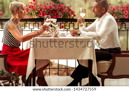 Enjoying romantic dinner. Couple of successful good-looking businessmen enjoying romantic dinner outside