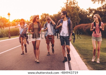Enjoying summer hike. Group of young people with backpacks walking together by the road and looking happy  #484943719
