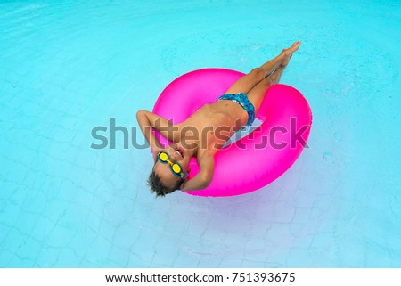enjoying sun vacation concept top view of funny boy in blue yellow swim glasses  on the pink air tube #751393675