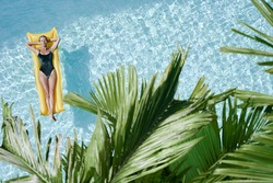 Enjoying suntan. Tropical vacation concept. Top view of young woman on the yellow air mattress in the swimming pool with palm trees.