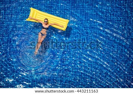 Enjoying suntan. Vacation concept. Top view of slim young woman in bikini on the yellow air mattress in the big swimming pool.