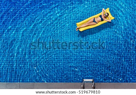 Enjoying suntan. Vacation concept. Top view of slim young woman in bikini on the yellow air mattress in the big swimming pool. #519679810