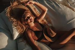 Enjoying suntan. Vacation concept. Top view of young  blond woman on the sun lounger near the swimming pool, relax, enjoy sunlight