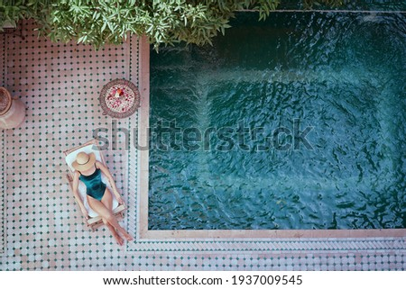 Enjoying suntan. Vacation concept. Top view of young woman on the sun lounger near  the private swimming pool in beautiful moroccan backyard. Stock photo ©