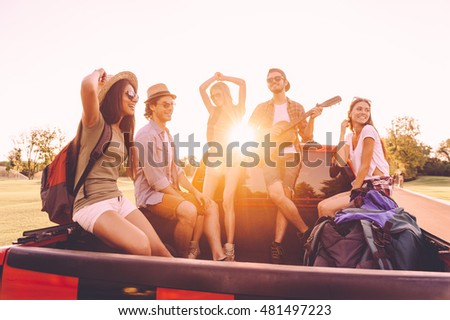Enjoying the best road trip ever. Group of young cheerful people enjoying their road trip while sitting in pick-up truck together  #481497223