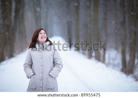 Enjoying the first snow: young woman outdoors on a lovely forest path watching the snowflakes falling (color toned image)
