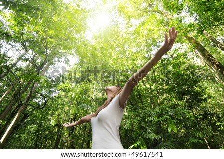 stock photo : Enjoying the nature. Young woman arms raised enjoying the fresh air in green forest.
