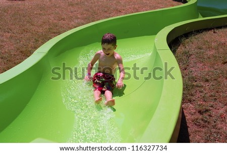 Enjoying the Slide/Young boy enjoys sliding  	down the water slide