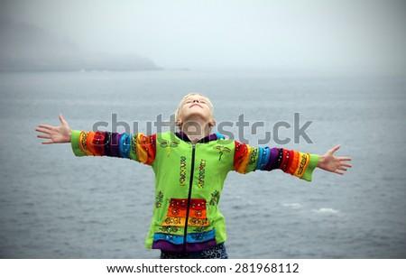 Enjoying the wind. Teenager girl arms raised enjoying the fresh ocean air. Freedom concept.