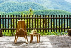 Enjoying time alone in nature concept. Wooden chair and flowers on terrace of country house and view of mountain landscape. Rural scene. Eco friendly lifestyle and travel. Rhodope Mountains, Bulgaria.