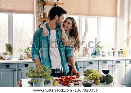 Enjoying time together. Beautiful young couple cooking dinner while standing in the kitchen at home