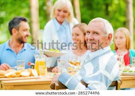 Enjoying time with family. Happy family of five people sitting at the dining table outdoors while senior man looking over shoulder and smiling