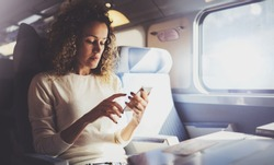 Enjoying travel concept. Young pretty woman tourist traveling by the train sitting near the window using smartphone