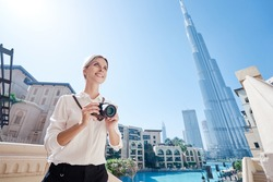 Enjoying travel in United Arabian Emirates. Happy young woman with camera taking photo in Dubai Downtown.