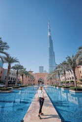 Enjoying travel in United Arabian Emirates. Young woman with camera walking on Dubai Downtown.