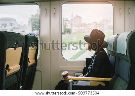Shutterstock Enjoying travel. Young pretty woman traveling by the japan classic train sitting near the window. vintage filter.