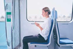 Enjoying travel. Young pretty woman traveling by the metro train sitting near the window using smartphone.