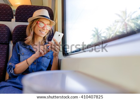 Enjoying travel. Young pretty woman traveling by the train sitting near the window using smartphone.