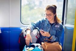 Enjoying travel. Young pretty woman with baggage traveling by the train or Mass Rapid Transit(MRT) train near the window using smartphone. Asian Lady Traveling Commute Train Concept.