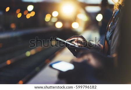Enjoying travel. Young woman waiting on station platform on background light electric moving train using smart phone in night. Tourist text message and plan route of stop railway, railroad transport #599796182