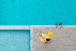 Enjoying vacation concept - Aerial view of Asian woman in yellow dress and summer hat relax around swimming pool in hotel resort for leisure in vacation. Selective Focus
