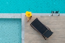Enjoying vacation concept - Aerial view of Asian woman in yellow dress and summer hat walking around swimming pool near chaise-longue in hotel resort for leisure in vacation.