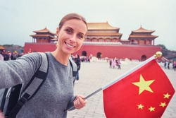 Enjoying vacation in China. Travel and technology. Young woman with national chinese flag taking selfie in Forbidden City.