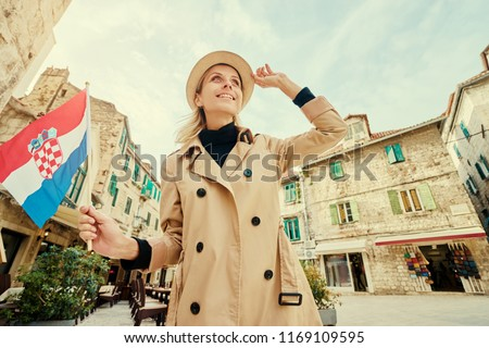 Enjoying vacation in Croatia. Young traveling woman with national croatian flag walking on Split Old Town.