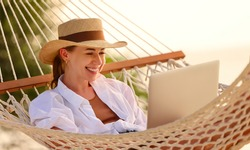 Enjoying work during summer vacation. Young happy woman, successful female freelancer in straw hat using laptop and smilingwhile relaxing in the hammock on the tropical beach. Distance job