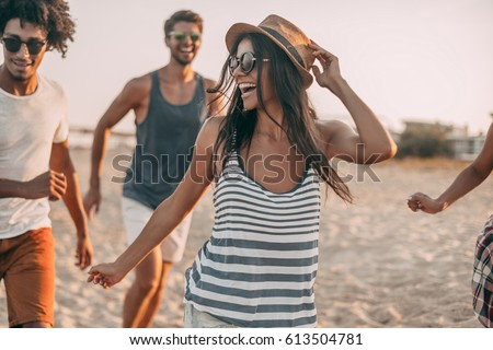Enjoying youth and freedom. Group of young cheerful people running along the beach and looking happy