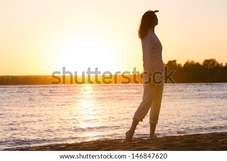 Enjoyment - free happy woman enjoying sunset. Beautiful woman in natural white shirt looking to the golden sunshine glow of sunset with arm near face enjoying peace, serenity in nature