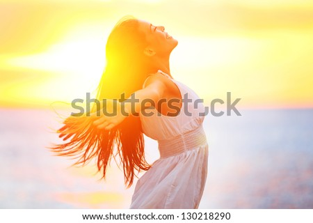 Shutterstock Enjoyment - free happy woman enjoying sunset. Beautiful woman in white dress embracing the golden sunshine glow of sunset with arms outspread and face raised in sky enjoying peace, serenity in nature