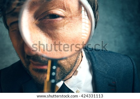 Shutterstock Enlarged eye of tax inspector looking through magnifying glass, inspecting offshore company financial papers, documents and reports.