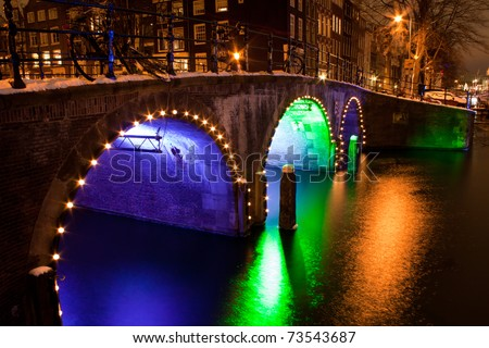 Enlightened bridge over canal in Amsterdam by night