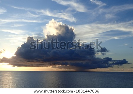 Enormous rain cloud above the sea, during sundown. Colourfull sky with clouds. local rain, Template for design of holiday greetings, decoration packaging, postcard, poster. atmosphere  perturbation Photo stock ©