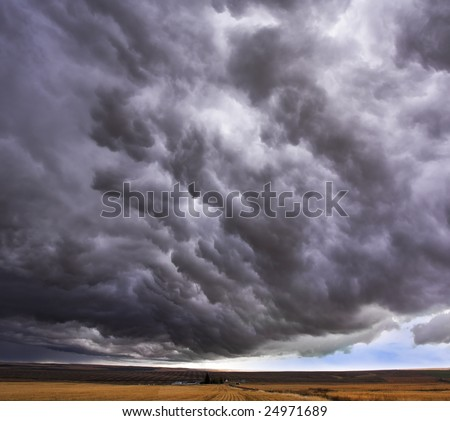 Enormous storm cloud above an autumn field
