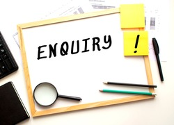 ENQUIRY text is written on a white office board. Work table with office supplies. Business and financial concept.