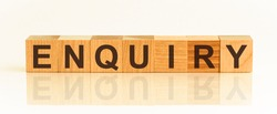 Enquiry word made with building blocks. Wooden Blocks with the text: Enquiry. The text is written in black letters and is reflected in the mirror surface of the table.