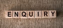 ENQUIRY word written on wooden blocks on a brown background.