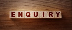 Enquiry word written on wooden blocks on wooden table.