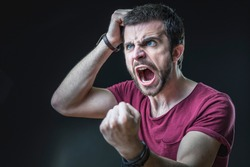 Enraged furious young man screaming in anger, pulling his hair out